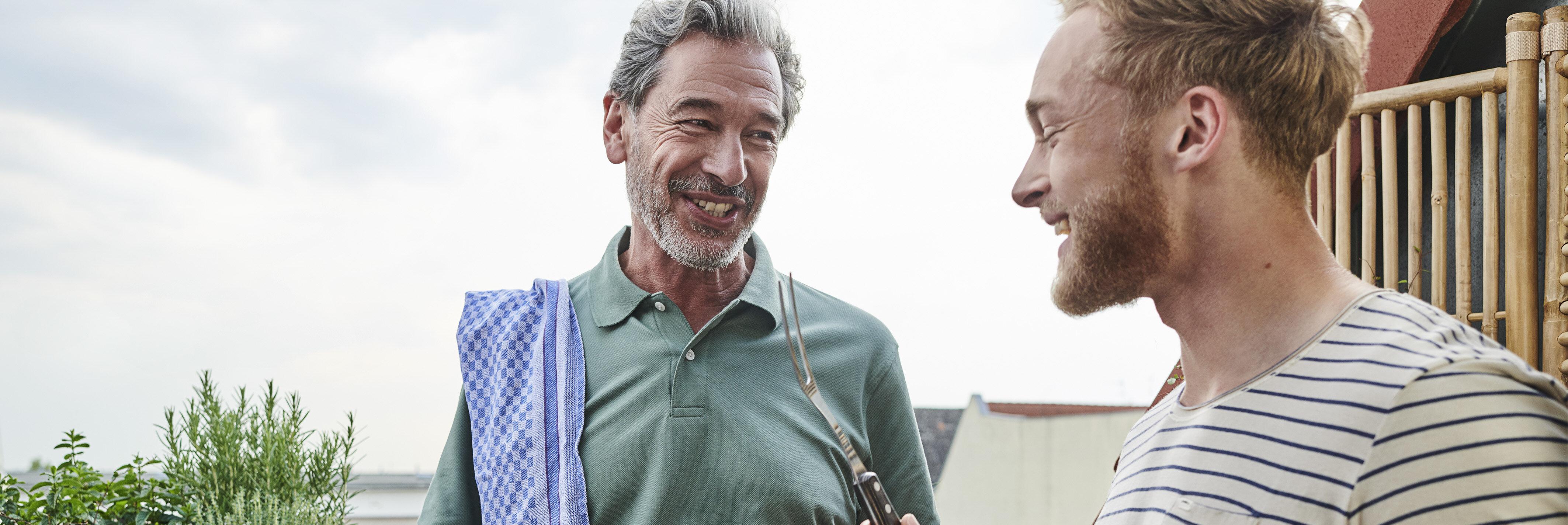 Zwei Männer unterhalten sich auf dem Balkon